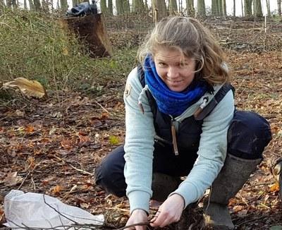 Scientist crouches on forest floor